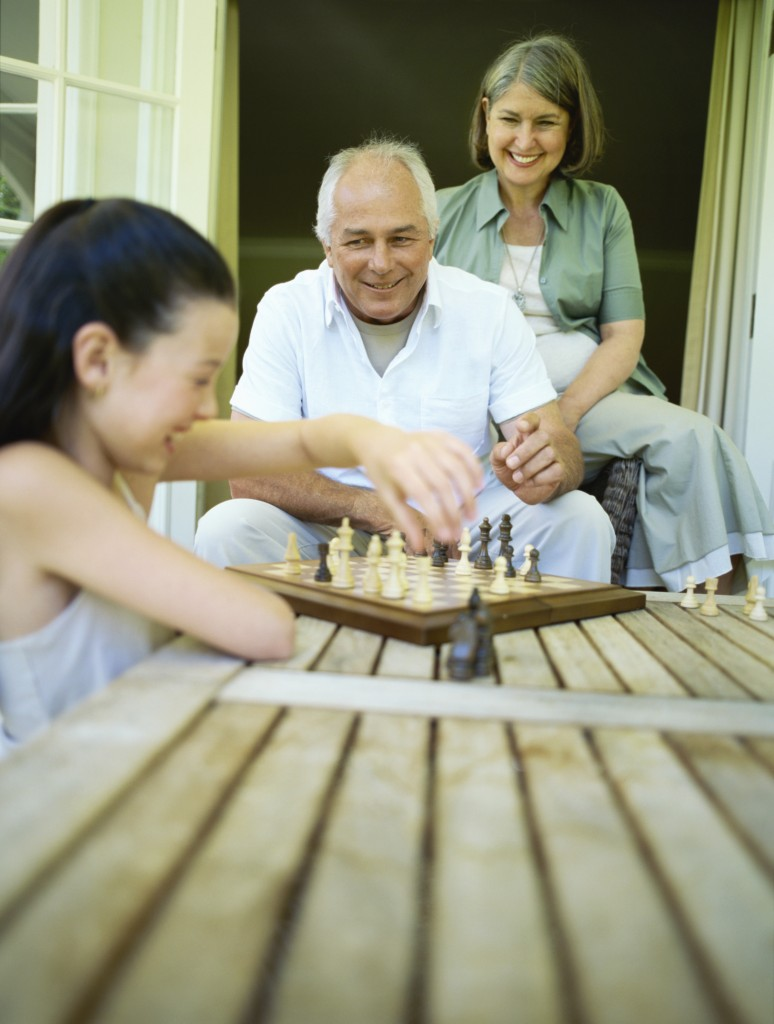 Girl playing chess with her grandparents