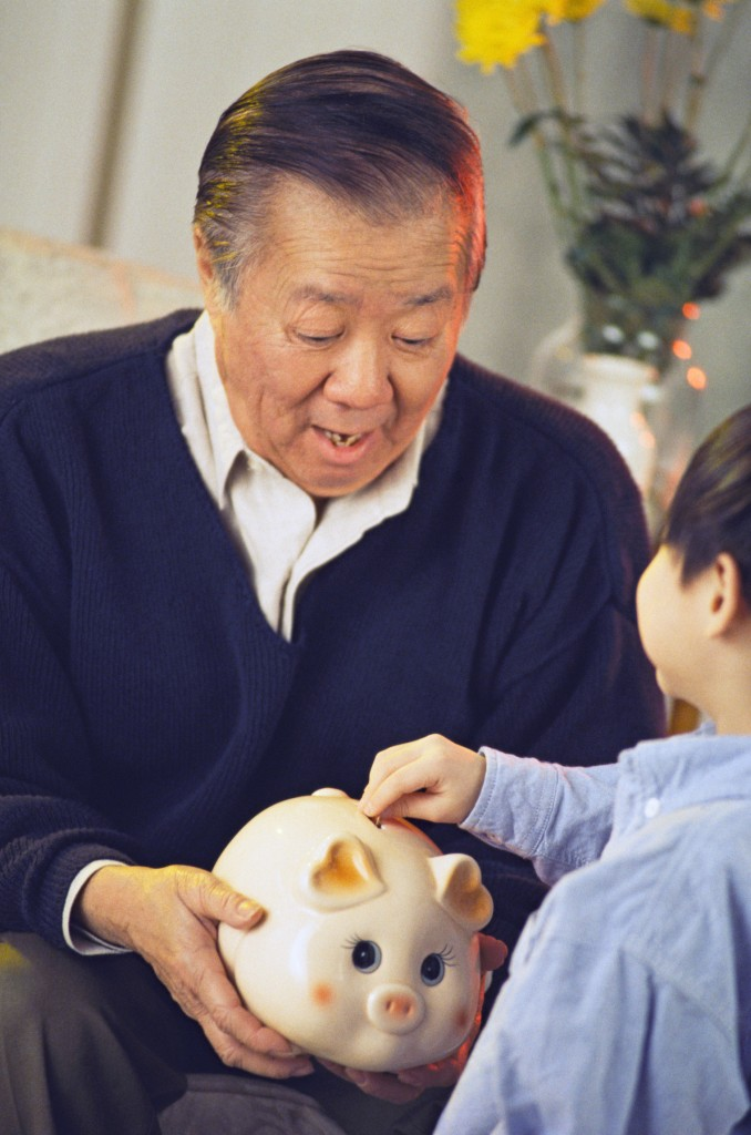 Boy deposits coin in piggybank held by grandfather