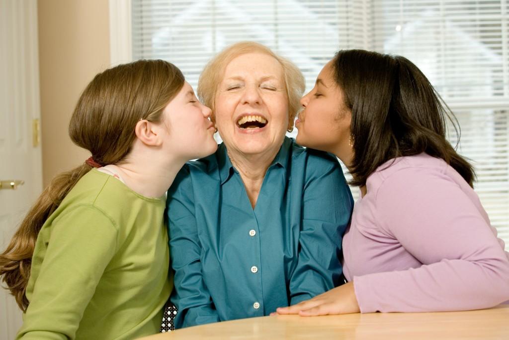Granddaughters kissing grandmother