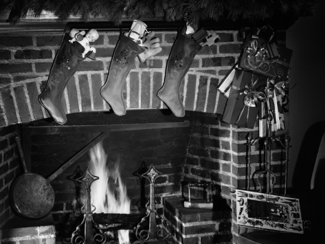 1950s-three-christmas-stockings-full-of-toys-hanging-over-brick-fireplace